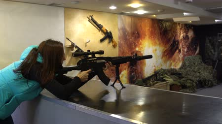 Shooting range. A woman in glasses aims and shoots from a Kalashnikov assault rifle. 影像素材