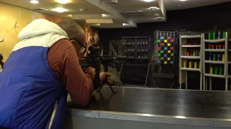 Shooting range. A man in glasses aims and shoots an M4 Carbine rifle at the bowling pins