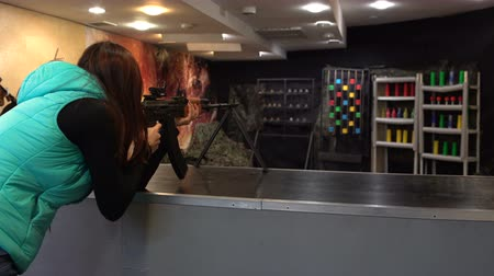 Shooting range. Woman in glasses aims and shoots a Kalashnikov machine gun in the dash 影像素材