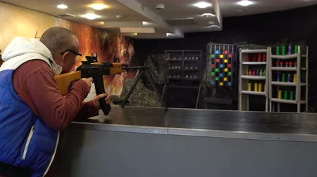 Shooting range. Man in glasses aims and shoots a PK machine gun in the dash at the targets