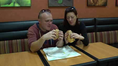 Woman and man in a cafe sits at a table and eats a sandwich.