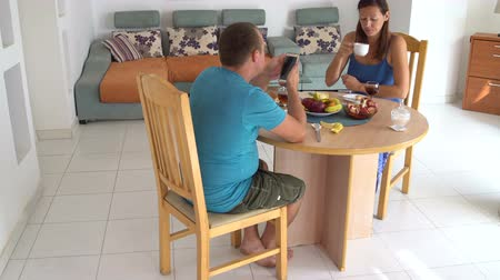 Husband and wife are sitting at the table at home and talking.