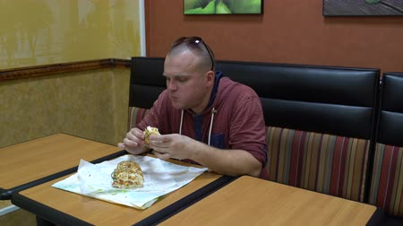 sajtburger : Man in a cafe sits at a table and eats a sandwich. Stock mozgókép