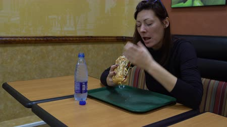 Woman eating a sandwich and drinking water in the Cafe