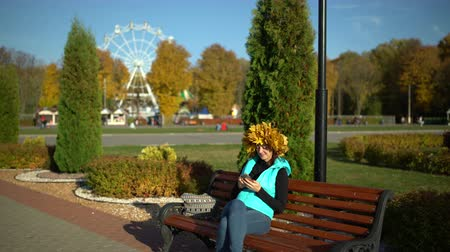 A woman sits on a bench in the Park and uses a smartphone