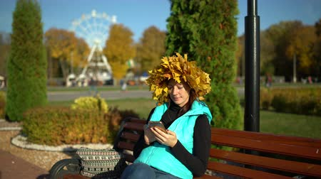 Woman with a maple wreath on her head sits on a park bench and uses a smartphone
