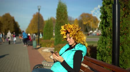 Woman with a maple wreath on her head sits on a park bench