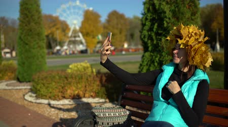 A woman with a maple wreath on her head taking a selfie on a smartphone