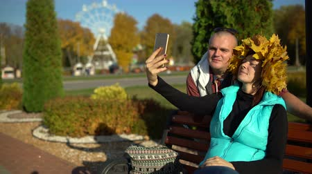A man and a woman with a maple wreath on her head taking a selfie on a smartphone
