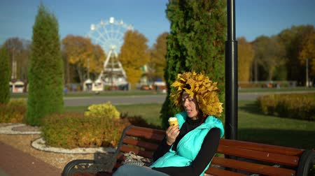 Woman eats ice cream in the Park on a bench