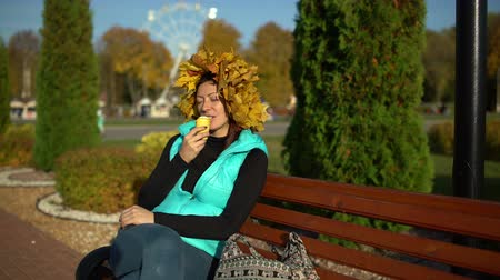 Woman with maple wreath on her head eats ice cream in a park on a bench