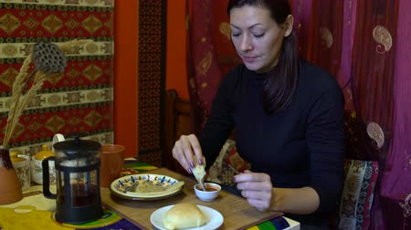 плоская маисовая лепешка : A woman in a cafe sits at the table and eats a cake dipping it into the sauce Стоковые видеозаписи