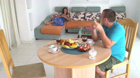 A man sits at a table eating a banana and talks to a woman. Woman lying on the sofa with smartphone