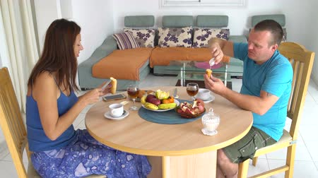 Family has breakfast at the table at home. Woman and man spread butter on bread and drink tea