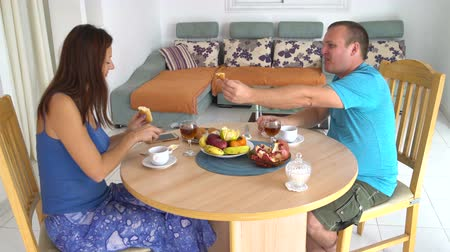 içecekler : Family having lunch at the table at home. Woman and man spread butter and honey on bread Stok Video