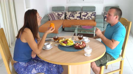 Husband and wife have breakfast at home. Woman eating persimmon. A man takes an apple Stock Footage