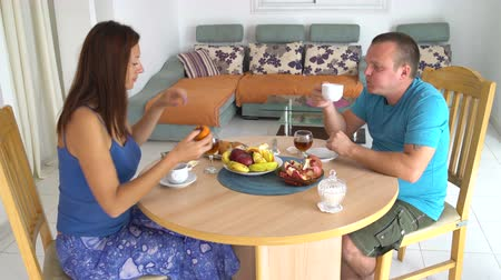 lunchen : Husband and wife have dinner at the table at home. Woman eating persimmon. Man drinking tea Stockvideo