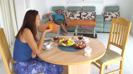 Woman eating persimmon sitting at the table. The man is lying on the couch eating an apple