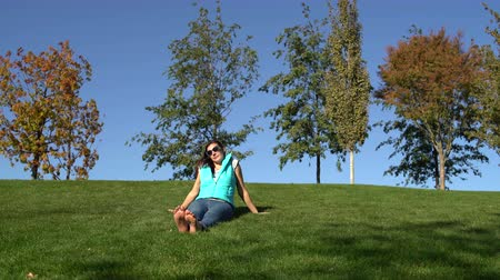 Woman sitting in the park on the green grass barefoot