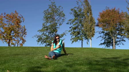 Woman sits in the park on the green grass barefoot and uses the smartphone 影像素材