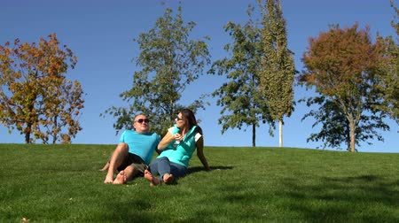 Woman and man are resting in the park sitting barefoot on the lawn
