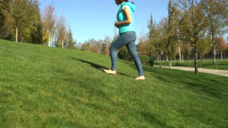 Woman in the park rises uphill on the green grass barefoot