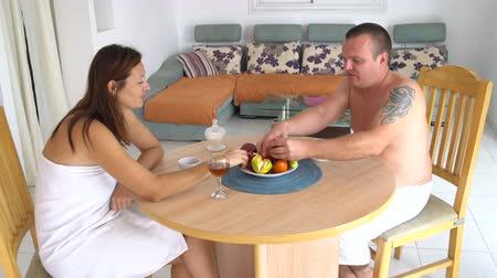 Man and woman sitting at the table eating fruit