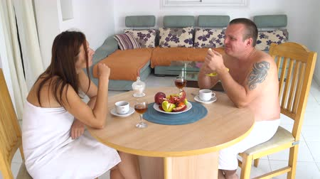 Man and woman in towels eat fruit sitting at the table at home in the living room and talking 影像素材