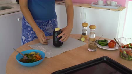 beringela : Woman cuts eggplant with a knife on a cutting board on a table in the kitchen