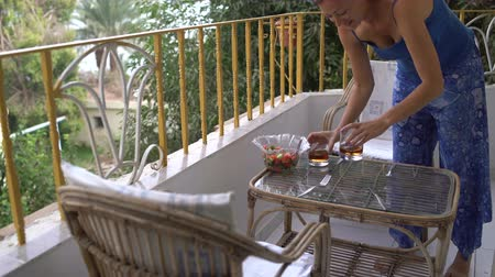 cognac : The woman sets the table. The girl puts the glasses with alcohol on the table on the balcony Stock Footage