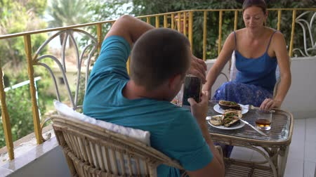 lunchen : Woman and man have breakfast sitting at the table. Man photographing woman on smartphone Stockvideo