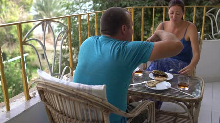 lunchen : Woman and man have a snack while sitting at the table. Man eating baked eggplant with his hands Stockvideo