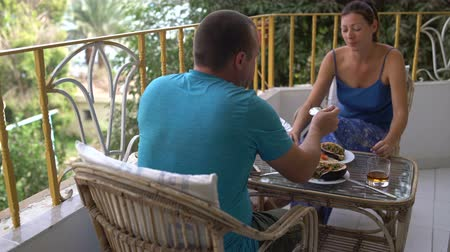 lunchen : Woman and man have lunch sitting at the table on the balcony. Man puts salad in plates Stockvideo