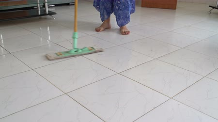mopping : Woman washes dirt from the floor with a mop
