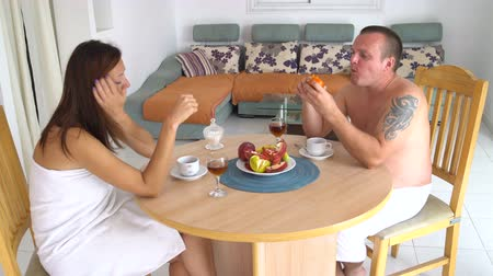lunchen : Man and woman in towels have breakfast sitting at the table at home in the living room and talking. Stockvideo