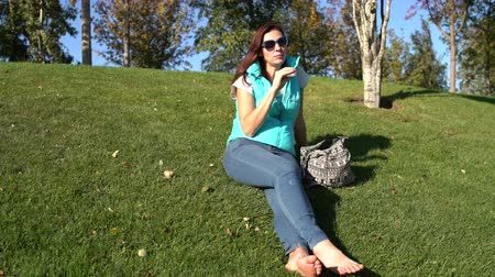 boso : Woman sits in the park on the lawn barefoot and eats patty