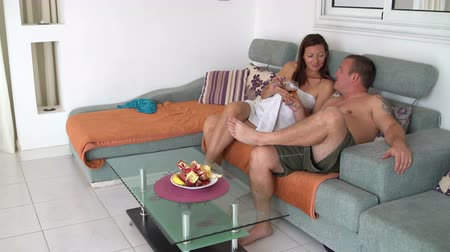 casal : A man and a woman are sitting on a sofa with a smartphone. A man drinks wine and treats a woman Stock Footage