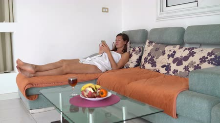 mentiras : A woman in a towel lies on the couch and uses a smartphone