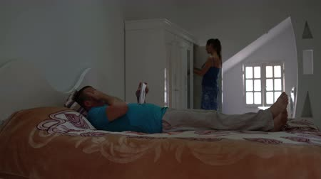 šatník : The man lies on the bed and uses the tablet pc. A woman walks to the closet and chooses clothes