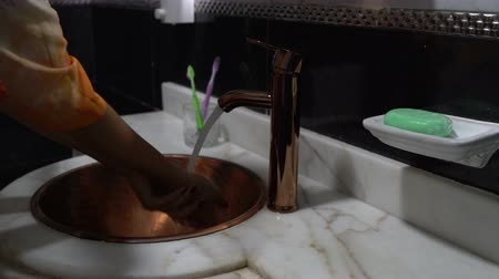 higiênico : Woman washes her hands under water in the sink in the bathroom