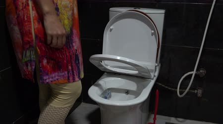 lids : Woman lowers the seat with microlift on the toilet