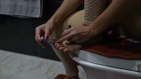 teennagels : Woman paints toenails with nail polish Stockvideo