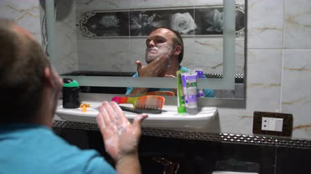 shaving foam : A man soaping face with soap in front of a bathroom mirror