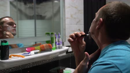 navalha : A man in the bathroom shaves in front of a mirror with a razor.
