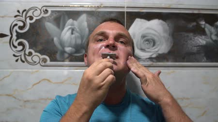 shaving foam : Man shaves his beard with a razor