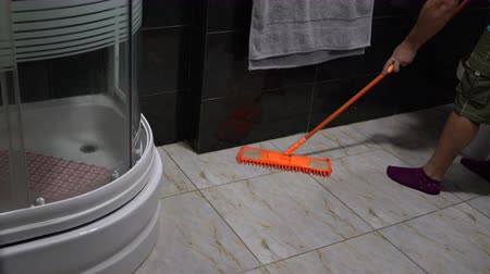limpador : A man washes floor tiles with a mop in the bathroom