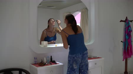губная помада : Woman paints eyelashes with mascara in front of a mirror Стоковые видеозаписи
