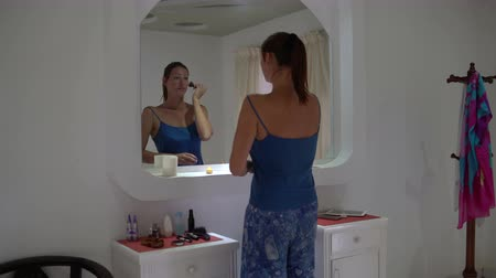tusz do rzęs : Woman applying powder with a brush in front of a mirror