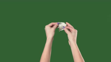 párat se : Green screen. Chromakey. Woman hands breaks the hundred dollar bill.
