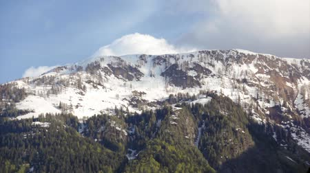 embléma : Video of clouds passing over a snow covered mountaintop in Carinthia, Austria. Stock mozgókép